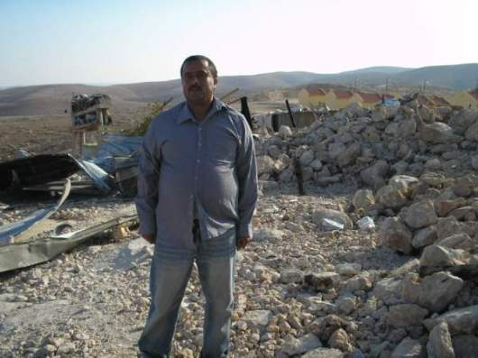 Umm-Al-Kheir resident and his ruined home. In the background the Carmel settlement